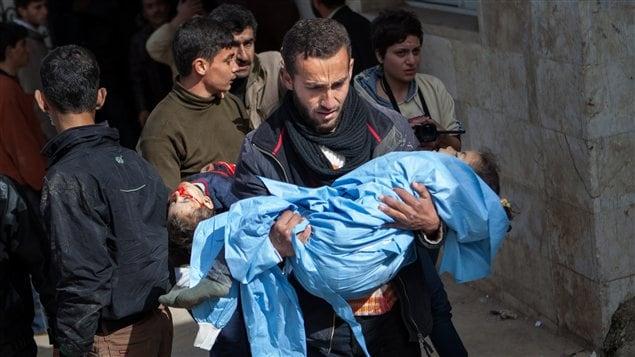 Deux jeunes enfants sont portés à la morgue à la suite d'un bombardement aérien contre la ville de Hass, dans le nord de la Syrie.