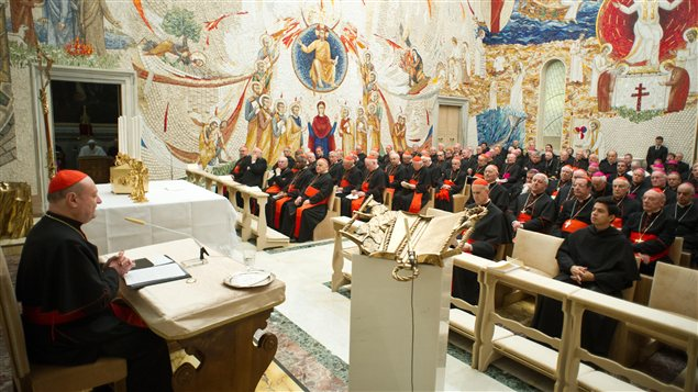 Un cardinal s&#39;adresse  ses confrres au Vatican, le 23 fvrier, tandis que le pape (dans la pice  gauche) prie.