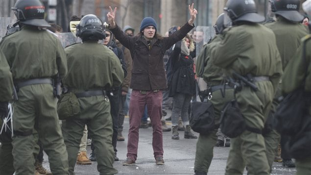 Un manifestant écarte victorieusement ses doigts en face de policiers de la SQ.