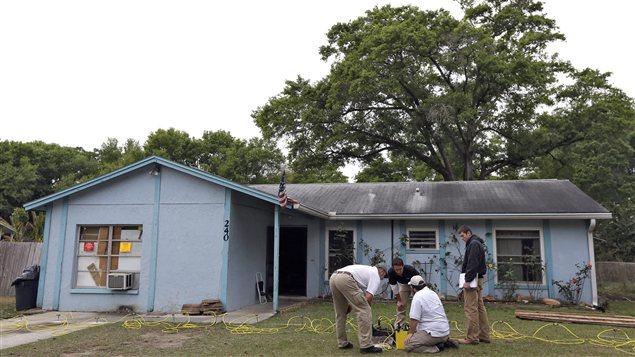 En Floride, des ingénieurs travaillent devant la maison au-dessous de laquelle s'est formé un gouffre qui a avalé un homme.