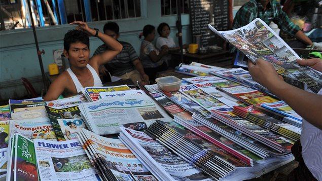 Devant un kiosque à journaux, un homme tient une copie du Voice daily, version quotidienne du magazine privé Voice, publié de façon hebdomadaire avant lundi. Photo prise au Myanmar le 1er avril 2013.