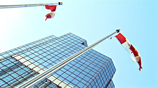 Des drapeaux canadiens devant un édifice fédéral à Ottawa.