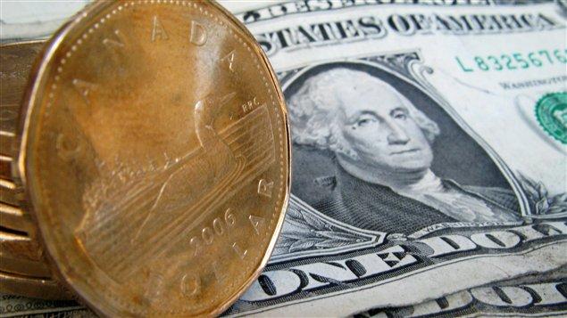 دولارات كندية معدنية على دولارات أميركية ورقية.