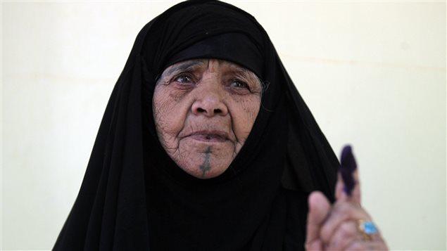 Une femme montre qu'elle a bien voté, lors des premières élections organisées en Irak depuis le départ des troupes américaines