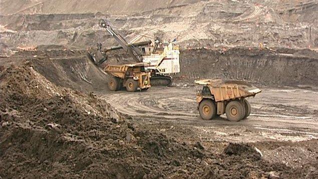 On gratte le sable bitumineux à l'aide de camions de 365 tonnes et des grues colossales, dont les pelletées font 100 tonnes.