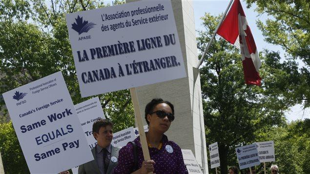 Des manifestants devant l'ambassade du Canada à Washington prostestent contre le désinvestissement du Canada en 2013 dans ses services de représentation à l'étranger.
