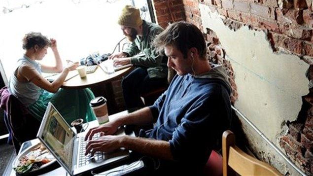 Un jeune homme magasine en ligne dans un café.