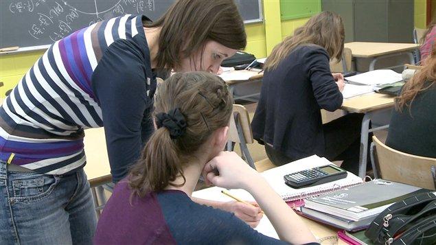 Une professeure aide une élève.