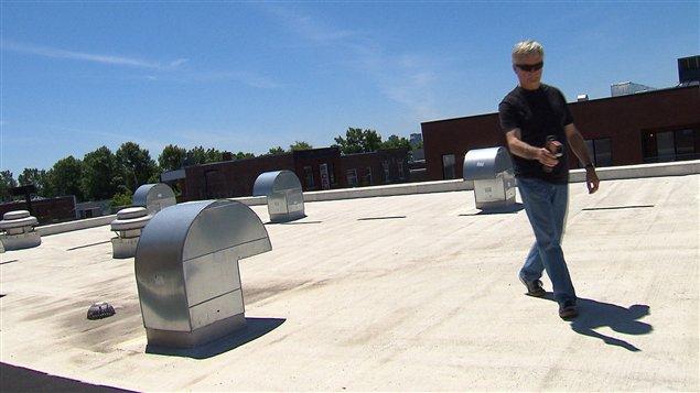 Le réalisateur Michel du Montier mesurant la température d'une des nouvelles toitures blanches du quartier La Petite-Patrie de Montréal.