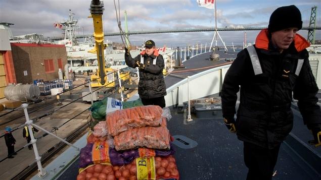 Chargement des marchandises à bord du bateau en préparation du départ en mer.