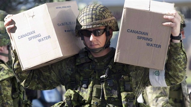 A Canadian soldier carries supplies as troops arrive at a temporary medical centre in Port-au-Prince, Haiti, Saturday January 16, 2010.