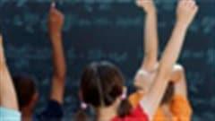 Des élèves lèvent la main pour répondre à une question