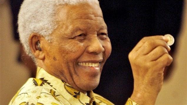 Nelson Mandela tient une pièce de 5 rands vendue à l'occasion de son 90e anniversaire.