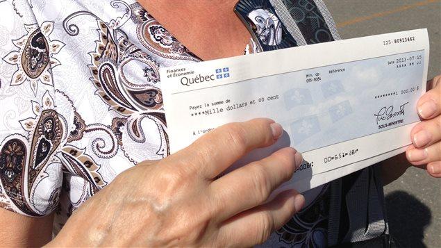 Une canadienne exhibe un chèque d'aide gouvernementale qu'elle a reçu.