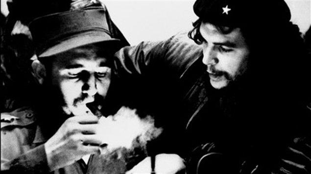 (Années 1960) Fidel Castro s'allume un cigare alors qu'il écoute son ami Ernesto Che Guevara.