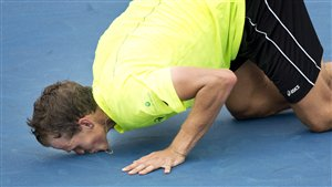 Vasek Pospisil on his knees kisses the blue court in Montreal.