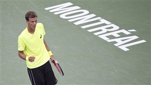 Vasek Pospisil clenches his fist as he walks off the court in yellow ti-shirt and black pants after his victory over Nikolay Davydenko on Friday.