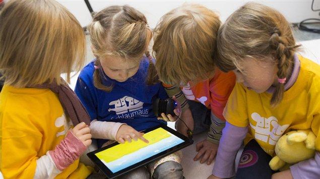 Des enfants s'int�ressent � une tablette num�rique