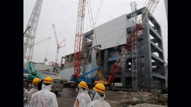 En juin 2013, des journalistes visitent le bâtiment d'un réacteur endommagé d'une centrale nucléaire de Fukushima | ©AFP/Noboru Hashimoto