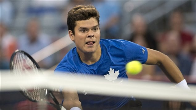 Milos Raonic in blue shirt with a white maple leaf its left breast finishes off a forehand volley Wednesday in Montreal. On Thursday, on a similar shot, Raonic hit the net with his foot but was not penalized.