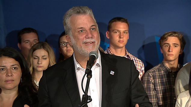 Philippe Couillard en conférence de presse, entouré de jeunes libéraux