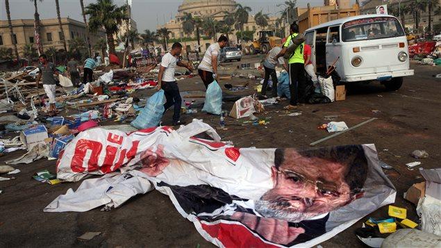 Des Égyptiens récupèrent des effets personnels dans les débris, au lendemain des violences au Caire.