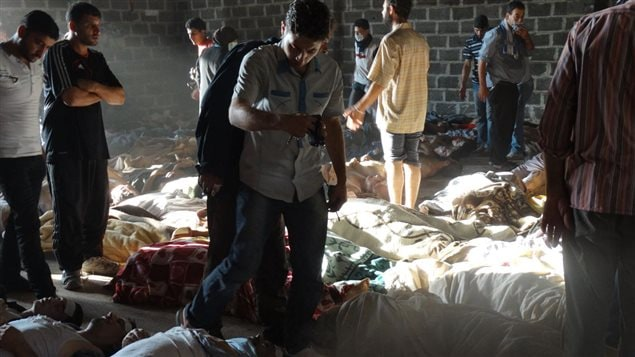 Image fournie par un groupe d'opposition syrienne qui montrerait des gens inspectant les corps de victimes de l'attaque au gaz neurotoxique dans des quartiers situés en périphérie de Damas, le 21 août.