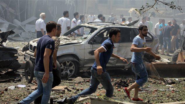 Des citoyens se précipitent sur les lieux de l'une des explosions qui ont secoué Tripoli, dans le nord du Liban.