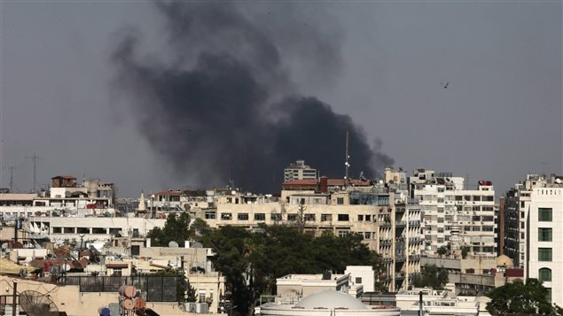 Black columns of smoke rise from heavy shelling in the Jobar neighborhood, east of Damascus on Sunday. Syrian state media said Syria reached an agreement with the United Nations on Sunday to allow a UN team of experts to visit the site of alleged chemical weapons attacks last week outside Damascus.