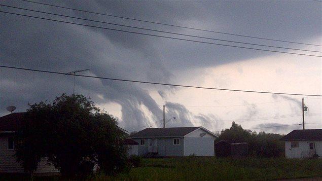 Des nuages en entonnoir s'élèvent du sol au ciel le dimanche 25 août 2013 dans la Première Nation Sagkeeng au Manitoba, durant le passage d'une tempête sur la rive nord de la réserve.