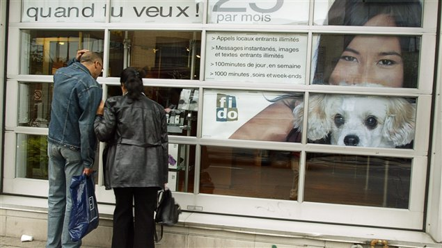 A man and a woman look through a shop window at wireless displays. On the right in the showroom are a teen-aged girl with a puppy at her chin.