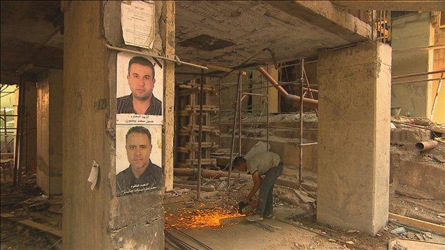 Les ouvriers à l'oeuvre et les photos des victimes sur les piliers des édifices