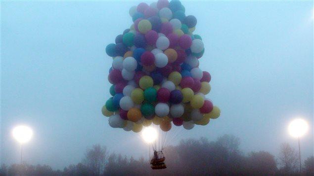 Un homme s'envole dans les airs à l'aide de ballons gonflés à l'hélium