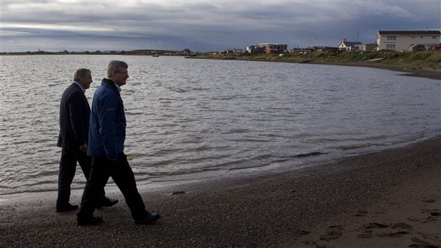 Prime Minister Stephen Harper, right, walks on the shore of the Beaufort Sea in 2010 with then .
