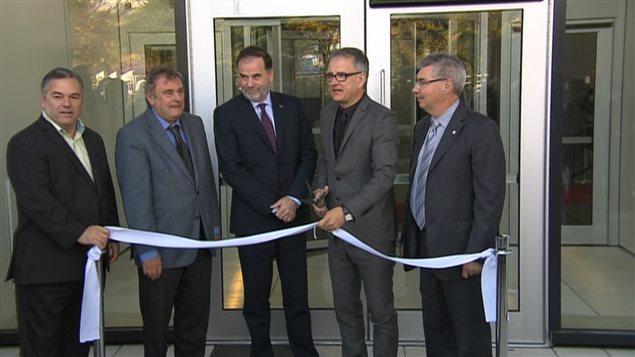 Le ministre Réjean Hébert coupe un ruban blanc pour inaugurer l'ouverture du Centre de recherche du CHUM