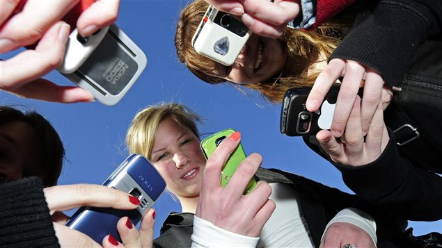 Des jeunes qui utilisent leur cellulaire