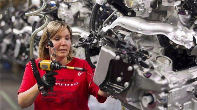 """عاملة متخصصة في مصنع """"جنرال موتورز"""" للسيارات في مدينة أوشاوا في أونتاريو، كبرى مقاطعات كندا ومحركها الاقتصادي (أرشيف)."""