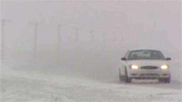 Une voiture roule lors d'une tempête hivernale