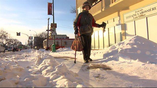 Une aînée se déplaçant à l'aide d'une canne s'aventure sur un trottoir enneigé dans le quartier Saint-Boniface de Winnipeg le 9 décembre 2013.