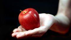 Une main tend une pomme