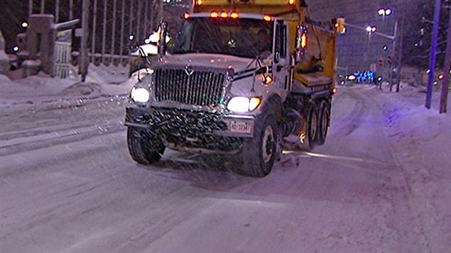 Un camion de la voirie à Ottawa épend des sels de déglaçage sur la chaussée.