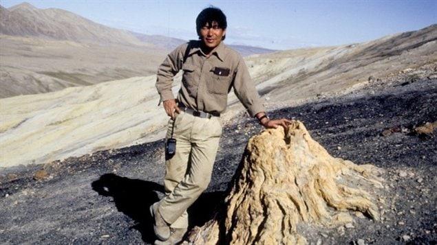 Dr. Tatsuo Sweda, de l'université de Nagoya au Japon  devant un tronc fossilisé près du Fjord Strathcona sur l'île d'Ellesmere au Nunavut en 1990.