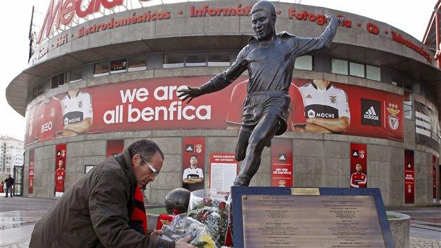 Un admirateur vient déposer des fleurs aux pieds de la statue d'Eusédio da Silva Ferreira devant le stade du club du Benefica à Lisbonne.