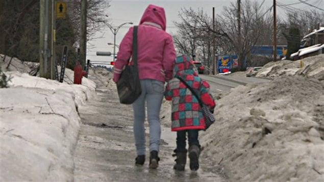 Des piétons sherbrookois bravent la glace sur les trottoirs.