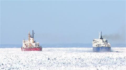 Un brise-glace de la Garde-Côtière aide un naviere marchant à se tracer un chemin dans les glaces du Fleuve Saint-Laurent.
