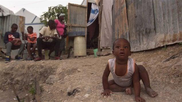 Un petit garçon est assis à côté de sa maison dans un camp de réfugiés à Port-au-Prince, quatre ans après le séisme qui a secoué Haïti.
