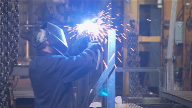 عامل لحام في مصنع في مدينة شاوينيغان في مقاطعة كيبيك (أرشيف).