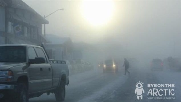 Someone crossing the street in Inuvik on a foggy winter day.