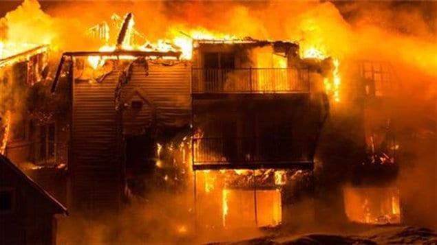 Le bâtiment de trois étages qui est complètement détruit. Il ne reste que des cendres fumantes de la partie de l'édifice qui a pris feu cette nuit.