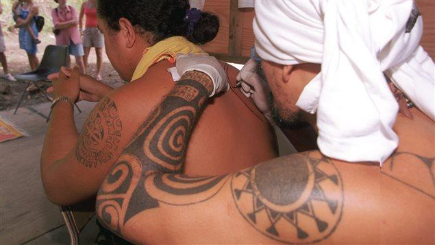 Un tatoueur en plein travail à Taputapuatea, en Polynésie